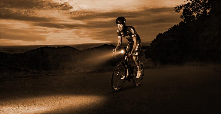 lampka rowerowa przednia rozświetla drogę przed rowerzystą